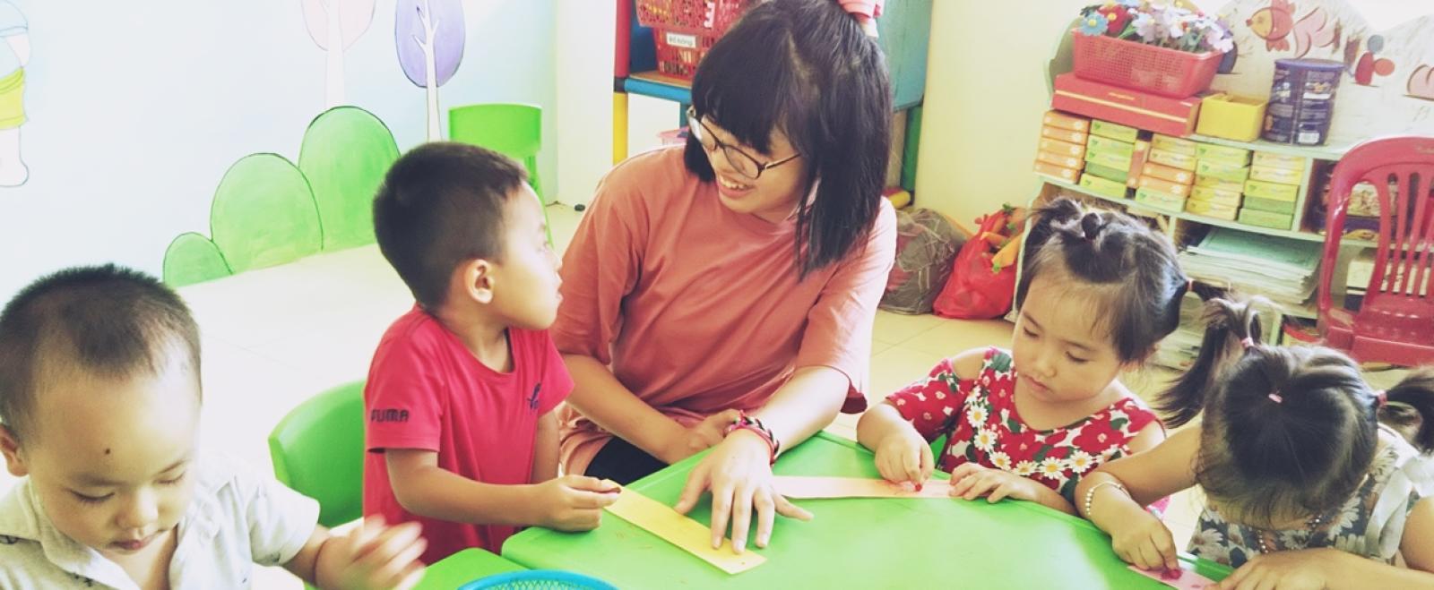 高校生ボランティア新村華子さんがベトナムの子供たちと七夕の短冊を作る